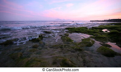Calm ocean at sunrise, small waves wash over the rocks on the beach with mountains in the background.
