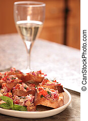 Bruschetta on a Plate With a Glass of White Wine