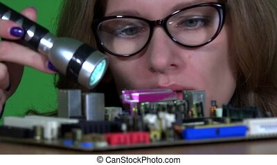 computer specialist girl with glasses examining computer motherboard main board