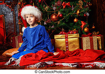 Christmas Eve - Christmas night. Little boy in pajama...