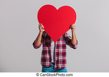 young casual man covers his face with big red heart