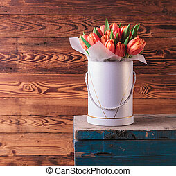 fresh spring flowers in a box on old wood background