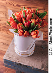 bunch of fresh orange tulips on a chair on wooden background