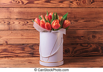spring tulips flowrs arrangement on old wood background in...
