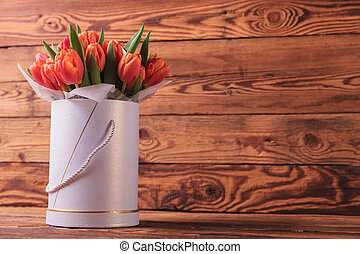 colorfull bunch of tulips in a round box on old wooden...