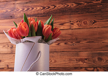 bouquet of tulips in a box on old wood background with copy...