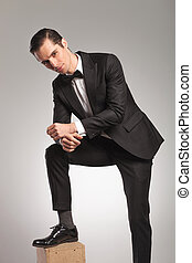man in tuxedo resting with leg up on wooden box