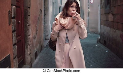 Portrait of young beautiful fashionable woman walking at...