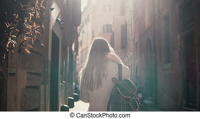 Back view of young woman walking at city street in Europe at...