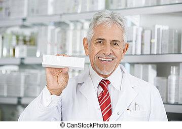 Smiling Pharmacist Holding Medicine Box Against Shelves
