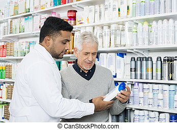 Pharmacist Assisting Customer In Buying Product