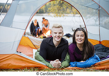 Young Couple Lying In Tent During Lakeside Camping
