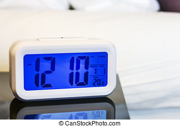 Alarm clock electronic stands on a bedside table near the...