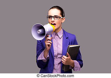 Young businesswoman with loudspeaker on gray background