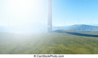 Wind turbine farm on green meadow, morning mist, tilt