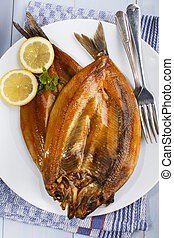 warm smoked kipper with lemon and parsley on a plate