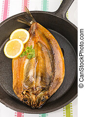 smoked kipper with lemon and parsley in a pan