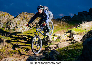 Enduro Cyclist Riding the Bike on the Rocky Trail at Night. Extreme Sport Concept. Space for Text.