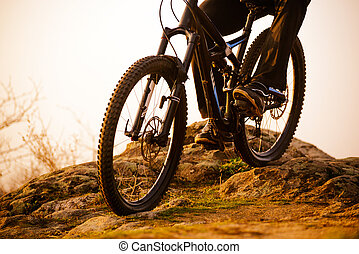Enduro Cyclist Riding the Bike Down Rocky Hill at Sunset. Close up Extreme Sport Concept. Space for Text.