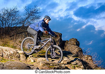 Cyclist Riding the Bike on the Rocky Trail at Sunset. Extreme Sport Concept. Space for Text.