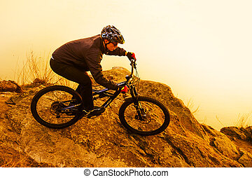 Enduro Cyclist Riding the Mountain Bike on the Rock. Extreme Sport Concept. Space for Text.