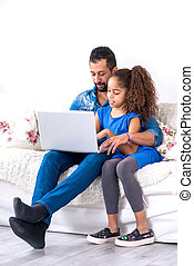 Black father and his daughter siting on a couch with a...