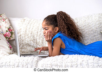 Black teenage girl siting on a couch with a laptop