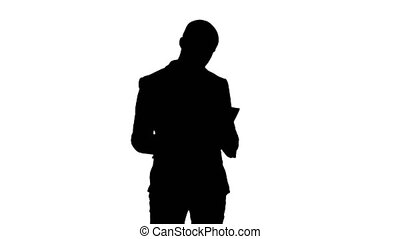 Silhouette Serious young businessman standing and reading...
