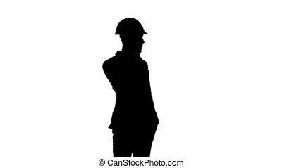 Silhouette Contractor in hardhat talking on his cell phone....
