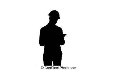Silhouette Engineer in hardhat looking at construction plan....