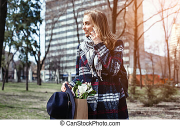 Young woman talking with boyfriend on cell telephone walking on a sunny day in the park. Beautiful girl in a coat, hat and flowers in the park in the spring