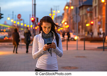 Young woman on the street with a phone - A beautiful young...