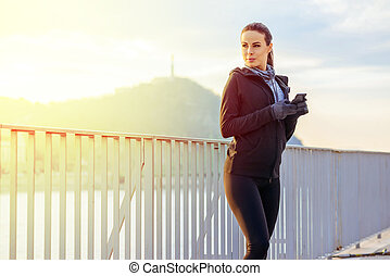 Young sporty woman standing in the sunset with a mobile