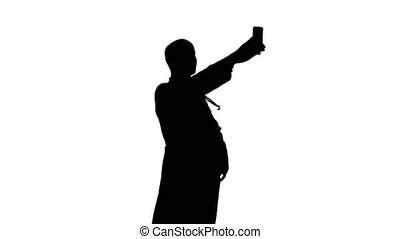 Silhouette Smiling doctor in white coat with stethoscope taking selfie on his phone