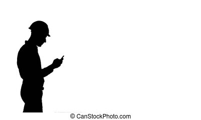 Silhouette Young manager in helmet using mobile phone. 065s....