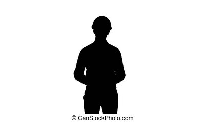Silhouette Happy young engineer in helmet talking to the...