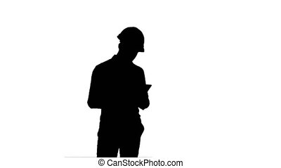 Silhouette Modern engineer using a wireless tablet to check construction project