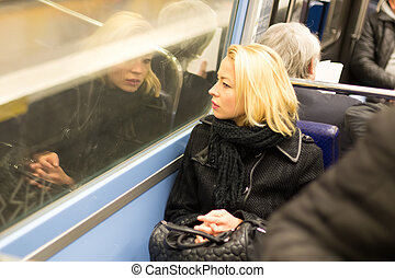 Woman looking out metro's window. - Thoughtful lady riding...