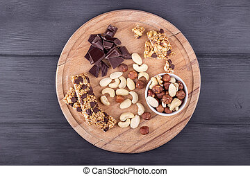 Granola bars, nuts, and chocolate on wooden cutting board....