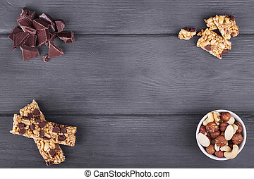 Variety of nuts, granola bars and chocolate on wooden...