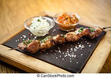 Iberian pork shish kebab with onion salad and sauce seved on...