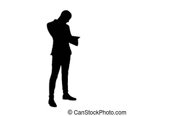 Silhouette Busy man talking on the phone and holding tablet....