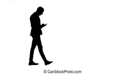 Silhouette Business man walks in checking up his phone
