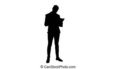 Silhouette Serious young manager standing and reading...