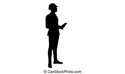 Silhouette Engineer in helmet carrying out inspection using...