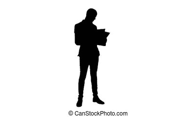Silhouette Young businessman attentively studying documents...