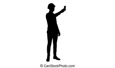 Silhouette Smiling construction worker using phone to take...