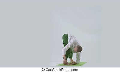 Handsome man doing yoga exercises on mat in studio
