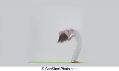 Woman doing yoga on mat in studio - Woman in white top and...