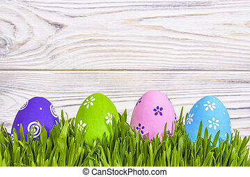 Pastel colored easter eggs in green grass over rustic wooden...